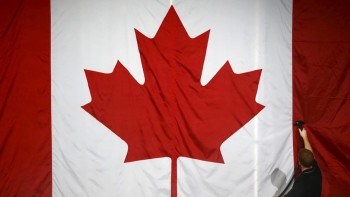 a-worker-steam-cleans-a-canadian-flag-in-preparation-for-mulcairs-election-night_16x9_WEB